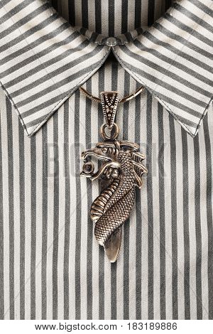 Bronze dragon pendant over striped satin blouse closeup as a background