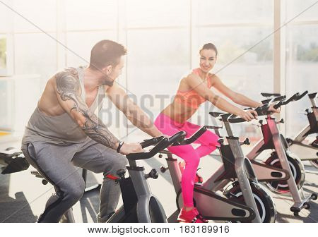Attractive couple in fitness club. Cardio workout on stationery exercise bikes. Healthy lifestyle, man and woman training in gym. Flare effect