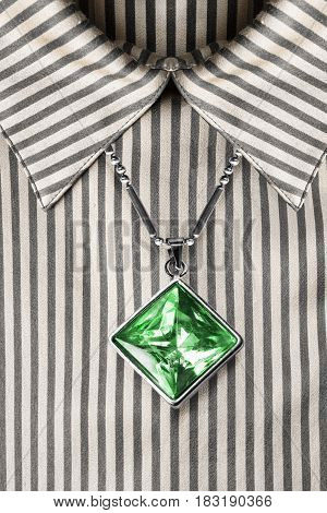 Large emerald pendant over striped satin blouse closeup as a background
