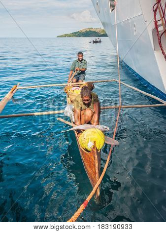 Hell-Ville Madagascar - December 19 2015: Malagasy vendors from their outrigger canoe offer fish and tropical fruits to ship passengers at Hell-Ville Nosy Be Island Madagascar.