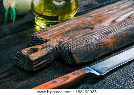 Rustic wooden cutting board, olive oil in cruet, onion bulb and chefs knife on old dark wood table. Close-up angle view