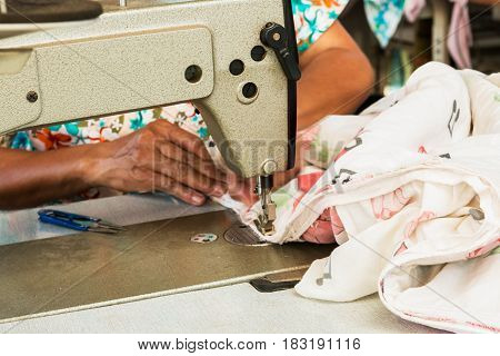Industrial sewing machines with workers being sewn.