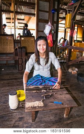 INLE, MYANMAR - MARCH 4 2017: Young burmese woman making thread from lotus flower in a floating village at Inle Lake on March 4, 2017, Myanmar.(Burma)