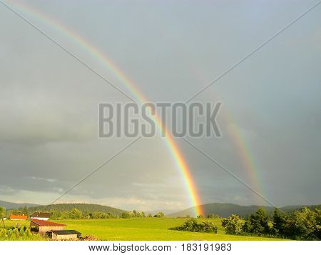 Rainbow view on a meadow with trees and a hill under a summer blue sky
