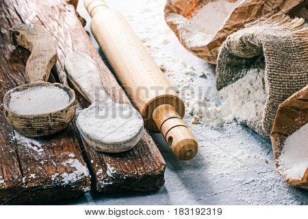 Packs of flour and sugar, rustic wood spoons and rolling pin on the concrete background. Close up