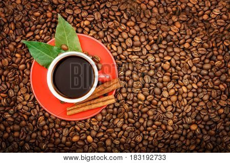 A red coffee cup with coffee and cinnamon is on roasted coffee beans.