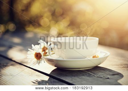 White porcelain cup and camomiles on a wooden table.