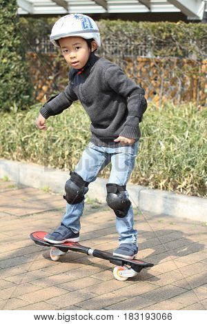 Japanese Boy Riding On A Casterboard (first Grade At Elementary School)