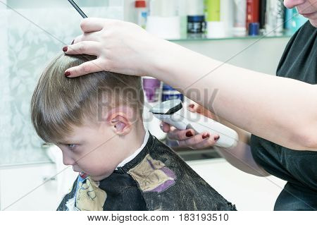 Little cute boy sitting in the chair at the hair salon. It cut Barber electric hair clippers white. In his left hand the master holds the comb. In the background are accessories.