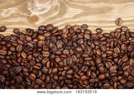 Roasted coffee beans on brown wooden background.