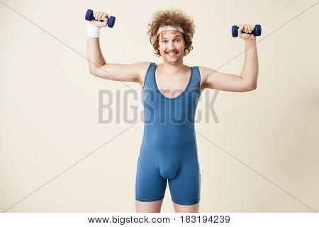 Closeup of young man in retro sport suit holding dumbbells in hands. Smiling at camera