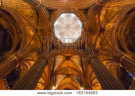 Old cathedral Interior looking straight up to the steeple.  Glowing columns of a sacred old church in Barcelona, crowned by sunlit steeple.  Old world building enduring the ages. Luminous & cavernous.