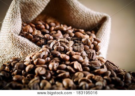 Bag of burlap filled with coffee beans on wooden background with blank tag.