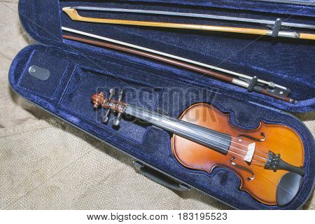 the violin in its case on the background of old sacking