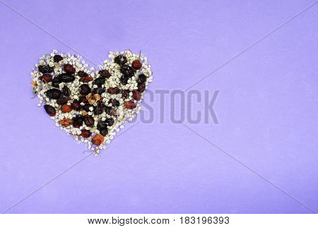 Heart from dried flowers pink violet purple background