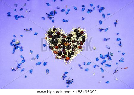 Heart of dried flowers pink violet purple background