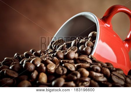 Red ceramic coffee Cup lying in the hot coffee beans. On a brown background.