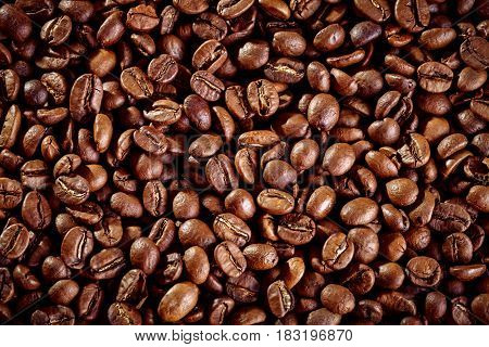 Brown background of fried coffee beans. Close-up.