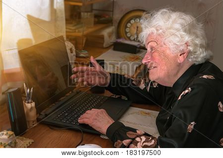 Happy merry grandmother learns to work at home on the computer and internet