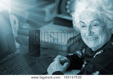 Happy grandmother sits at the table with a computer before learning to use the Internet blue tone