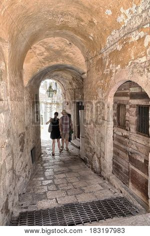 tourist couple narrow alley in Dubrovnik Old Town, Croatia