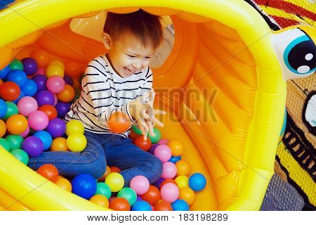 Boy playing with colored balls in the bouncy house at the Playground in the room. Colorful plastic balls the joy on a child's face a playful and funny guy.