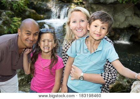 Multiracial Family Enjoys A Tourist Holiday At The Edge Of A Waterfall