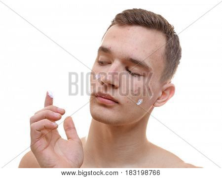 Handsome young man applying cream for problem skin onto face, on white background