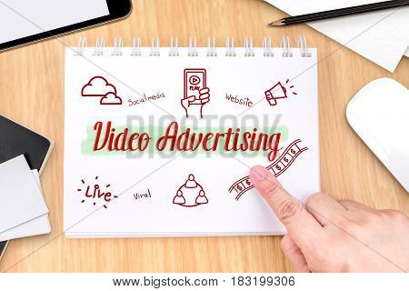 Hand Pointing At Video Advertising On Book With Hand Drawn Feature Icon On Wood Table With Tablet, P