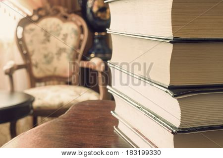A stack of books on the table in a home setting.