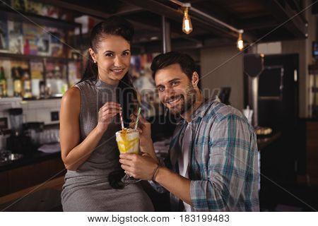 Portrait of happy couple having milkshake in restaurant