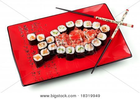 Sushi in the shape of the fish with chopsticks on the red plate. poster