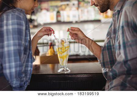 Couple having milkshake at counter in restaurant