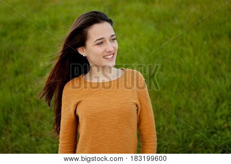 Outdoor portrait of beautiful happy teenager girl laughing with perfect teeth in field