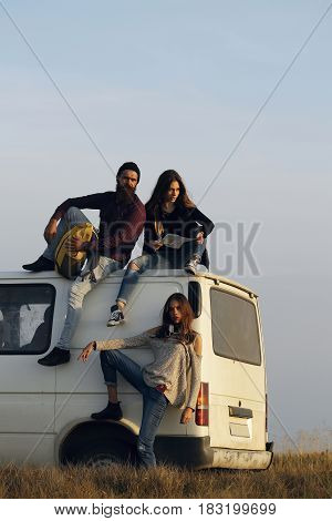 Young people handsome man and pretty girls travel by minibus and find direction destination on map on mountain top on foggy sky