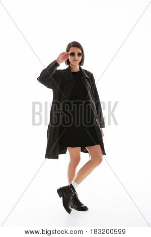 Picture of concentrated young lady wearing sunglasses standing isolated over white background. Looking at camera.