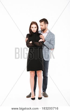 Picture of offended young loving couple swear isolated over white background. Man ask for apologize.