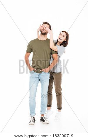Image of smiling young loving couple standing isolated over white background. Woman looking aside while covering man's eyes.