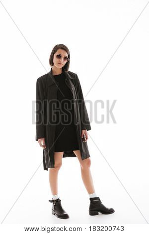 Picture of serious young lady wearing sunglasses standing isolated over white background. Looking at camera.