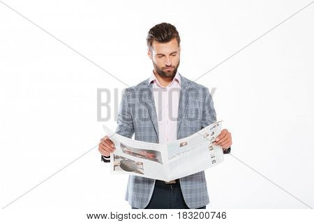 Picture of concentrated young man standing isolated over white background and reading gazette. Looking aside.