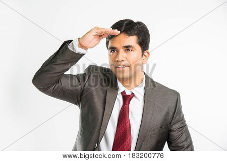 Possibilities for business concept - Indian young Businessman trying to look beyond or something at long distance or trying to focus on something or with bad vision, isolated over white background