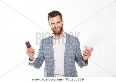 Image of smiling young man standing isolated over white background while holding gazette and mobile phone. Looking at camera.