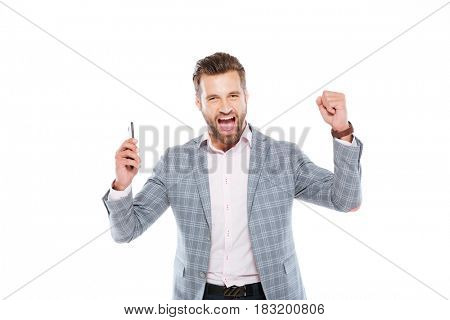 Picture of smiling young man standing isolated over white background and using mobile phone. Looking at camera make winner gesture.
