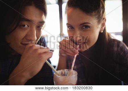 Portrait of couple having milkshake in restaurant