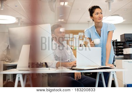 Business colleagues looking away seen through glass at office