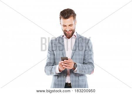 Image of happy young man standing isolated over white background and using mobile phone. Looking aside.