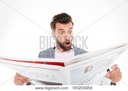 Picture of shocked young man standing isolated over white background while reading gazette. Looking aside.