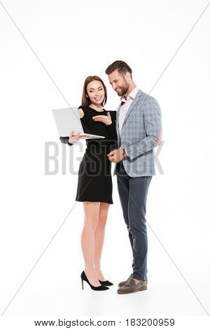 Image of happy young loving couple standing isolated over white background. Looking aside while using laptop computer.