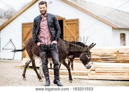 Handsome businessman with donkeys outdoors a the household