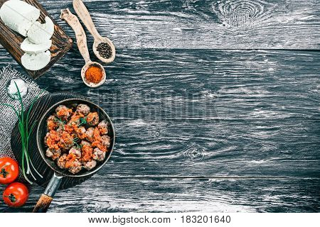 Fried meatballs on frying pan on black and white wood background with fresh tomatoes, homemade cheese and spices